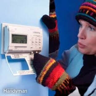 Cold woman near thermostat